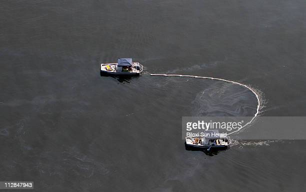 Boats in the Vessels of Opportunity program use boom to collect oil in the Mississippi Sound from the Deepwater Horizon oil spill Friday July 9 2010