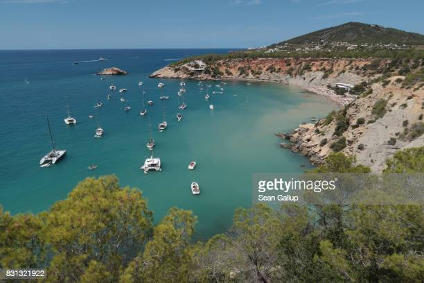 Boats lay anchored at Cala d'Hort beach on the island of Ibiza on August 11 2017 near Sant Josep Spain Ibiza is a popular tourist destination