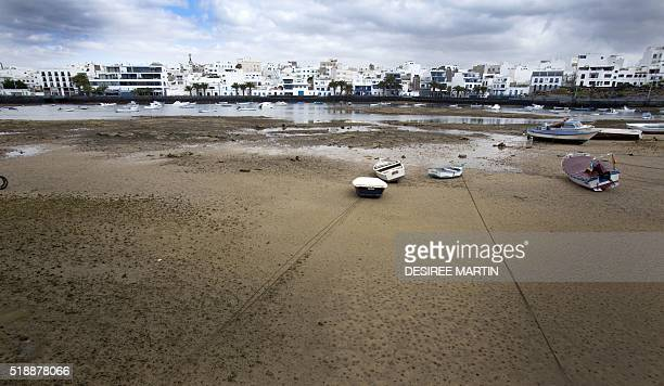 Boats lie at low tied in the port of San Gines in the capital of Lanzarote Arrecife on the Spanish Canary island of El Lanzarote on March 23 2016 /...