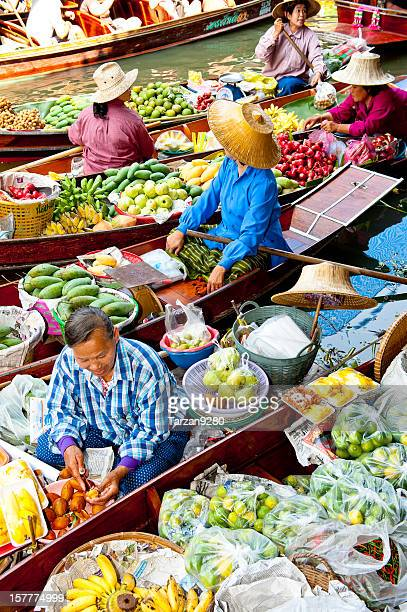 boats loaded with fruits in damnoen saduak floating market, thailand - floating market stock photos and pictures