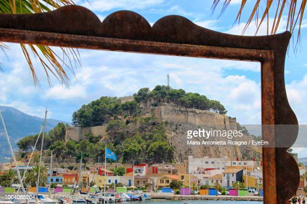 boats moored against castle seen through frame - denia stock pictures, royalty-free photos & images