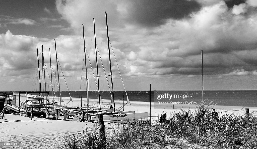 Boats Moored Against Cloudy Sky On Beach : Stock Photo