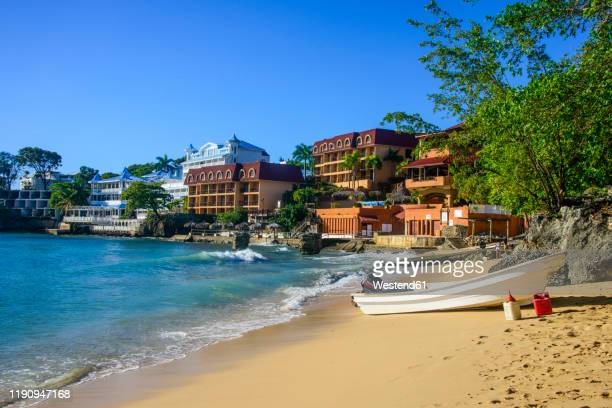 boats moored at beach against clear blue sky in sosa, dominican republic - dominican republic stock pictures, royalty-free photos & images