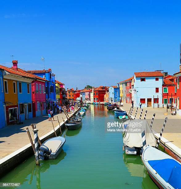boats moored at canal with houses in background - venice foto e immagini stock