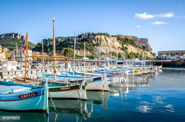 boats moored at harbor against blue sky - cassis stock pictures, royalty-free photos & images