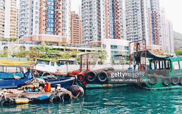 boats moored at harbor against buildings in city - amanda and amanda stock pictures, royalty-free photos & images