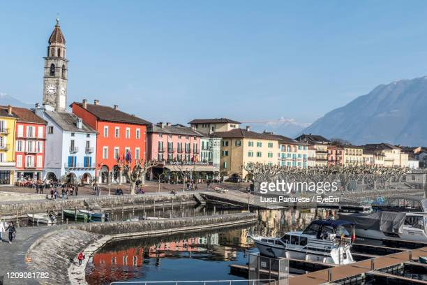 boats moored at harbor against buildings in city - ascona stock pictures, royalty-free photos & images