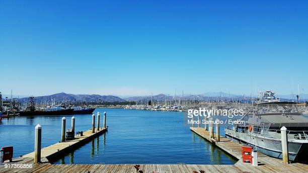 boats moored at harbor against clear blue sky - simi valley stock photos and pictures