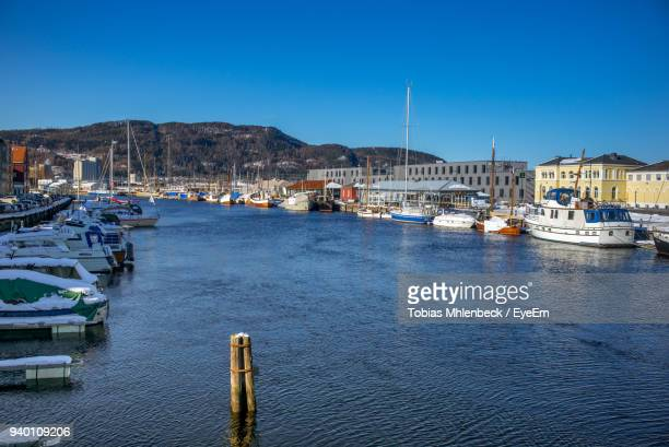 Boats Moored At Harbor Against Clear Blue Sky