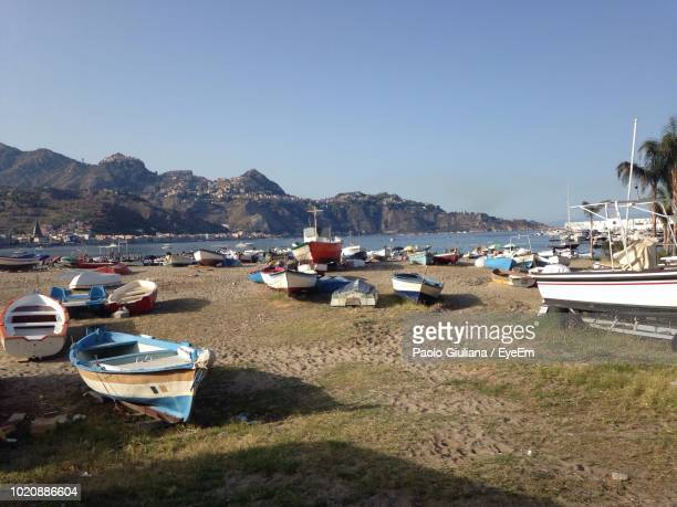 boats moored at harbor against clear sky - giardini naxos stock pictures, royalty-free photos & images