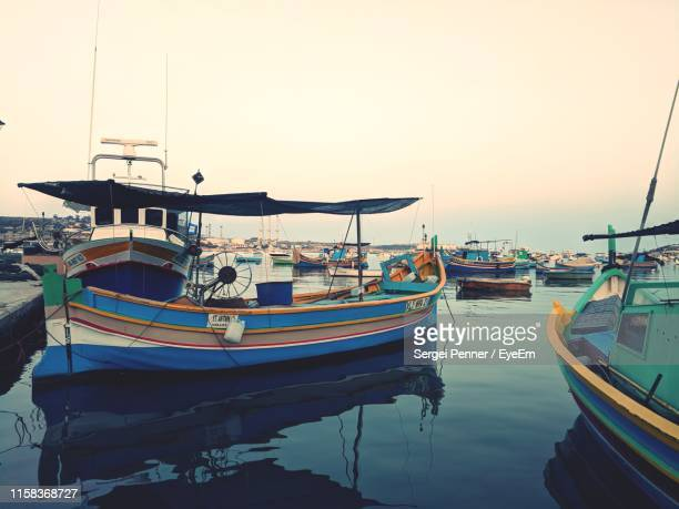boats moored at harbor against clear sky - marsaxlokk stock pictures, royalty-free photos & images