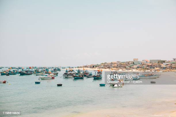 boats moored at harbor against clear sky - cameroon stock pictures, royalty-free photos & images