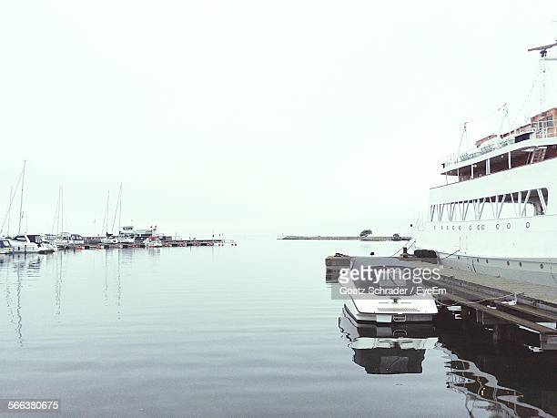 Boats Moored At Harbor Against Clear Sky