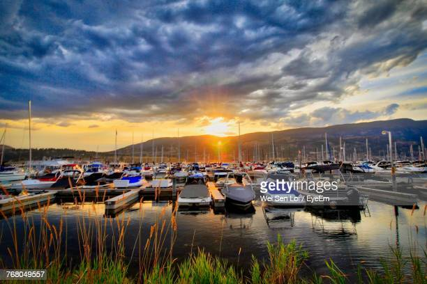 boats moored at harbor against sky during sunset - kelowna stock pictures, royalty-free photos & images