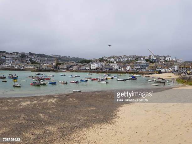 boats moored at harbor against sky in city - st ives stock pictures, royalty-free photos & images