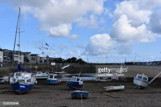 boats moored at harbor against sky - low tide stock pictures, royalty-free photos & images