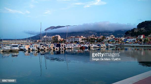 boats moored at harbor against sky - denia stock pictures, royalty-free photos & images