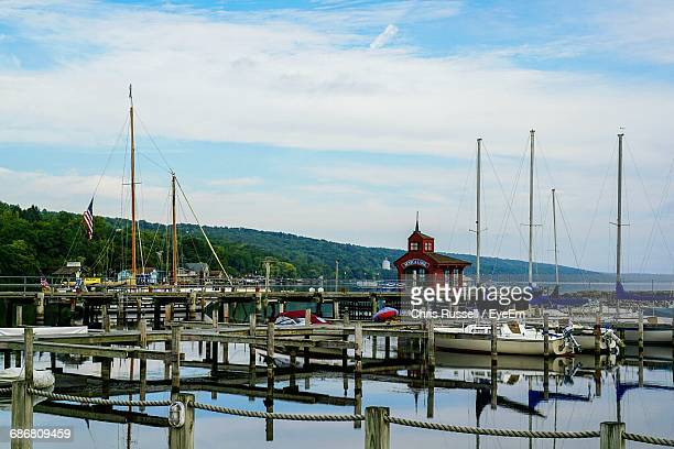 boats moored at harbor against sky - watkins glen stock photos and pictures