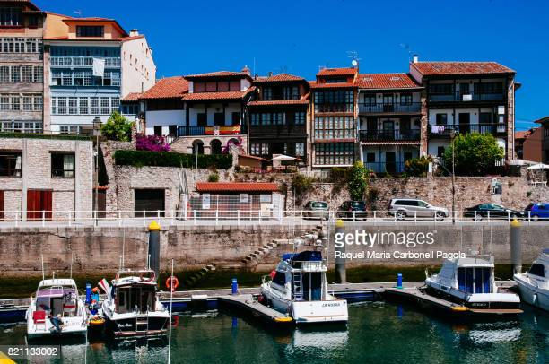 Boats moored at harbor and village houses