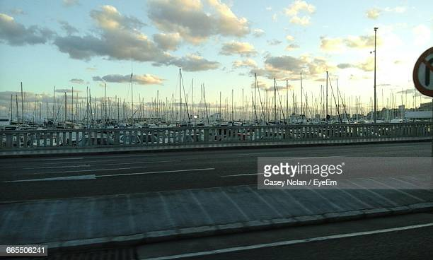 boats moored at harbor by bridge against sky - casey nolan stock pictures, royalty-free photos & images