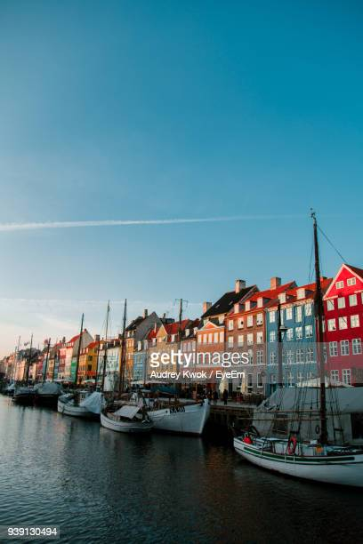 boats moored at harbor by buildings against sky - copenhague photos et images de collection