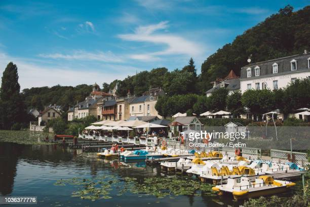 boats moored at harbor by buildings in city against sky - oise stock pictures, royalty-free photos & images