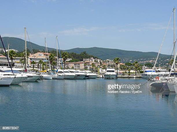 boats moored at harbor by houses against sky - var stock-fotos und bilder
