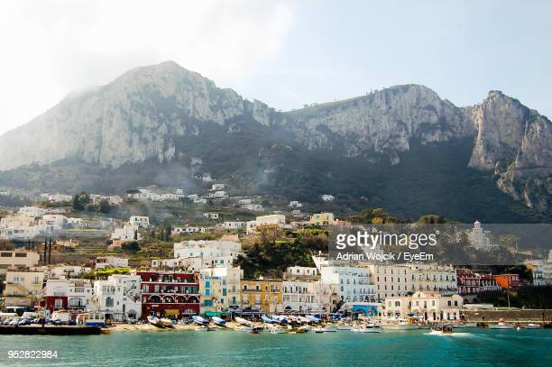boats moored at harbor by mountains against sky - capri stock pictures, royalty-free photos & images