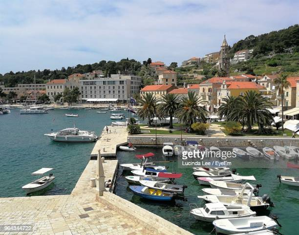 boats moored at harbor in city - lucinda lee stock photos and pictures