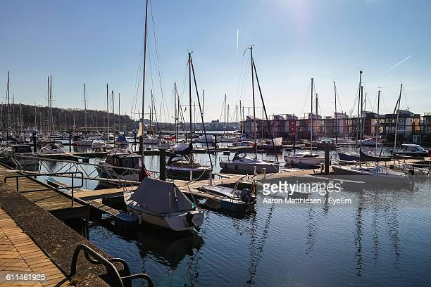 Boats Moored At Harbor In Sea Against Sky