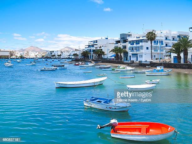 boats moored at harbor in sea by buildings against sky - arrecife stock photos and pictures