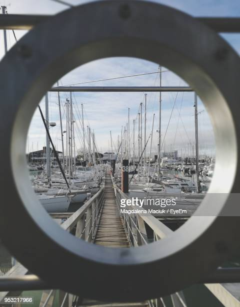 boats moored at harbor seen through hole - la rochelle stock pictures, royalty-free photos & images