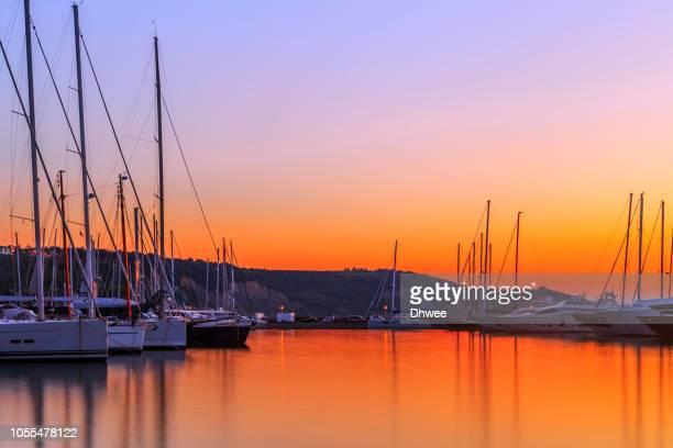 boats moored at jagodje harbor against vibrant and beautiful sunset - puerto deportivo puerto fotografías e imágenes de stock