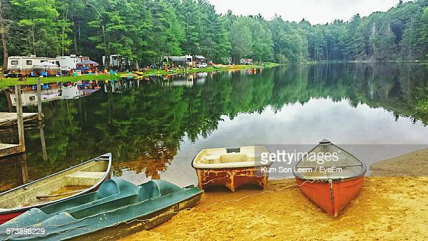boats moored at lakeshore in forest - sturbridge stock photos and pictures