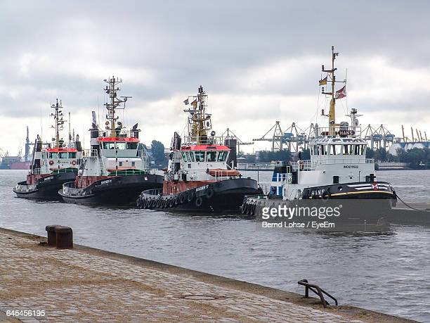 boats moored at river against cloudy sky - tugboat stock photos and pictures