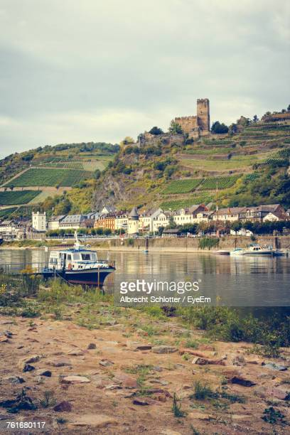 boats moored at riverbank against cloudy sky - albrecht schlotter stock photos and pictures