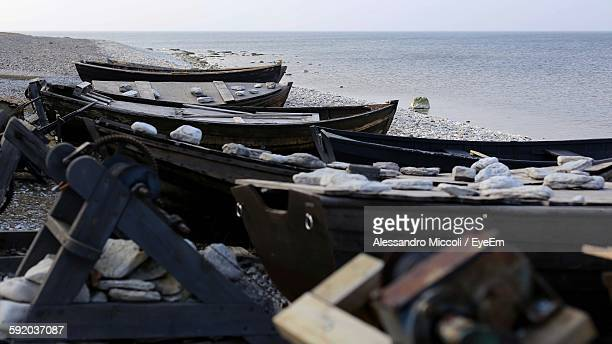 boats moored at shore at beach - alessandro miccoli stockfoto's en -beelden