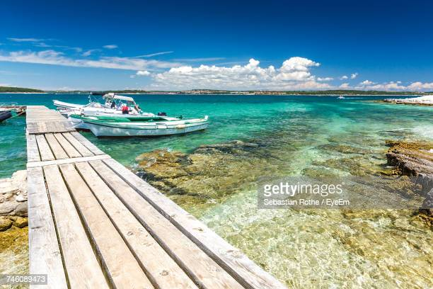 boats moored by jetty in sea against sky - イストリア半島 プーラ ストックフォトと画像