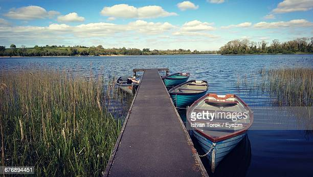 Boats Moored By Pier At Lake Against Sky