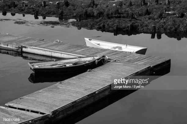 Boats Moored By Pier On Lake Against Sky