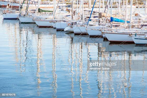 boats moored in a row in harbor - marina stock photos and pictures