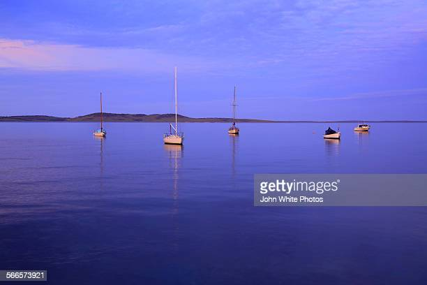 boats moored in boston bay at sunset. - calm before the storm stock pictures, royalty-free photos & images