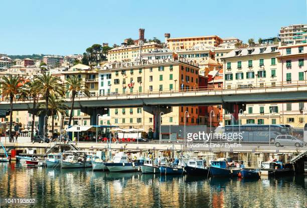 boats moored in canal against buildings in city - genoa italy stock pictures, royalty-free photos & images
