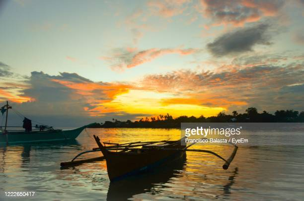 boats moored in canal against sky during sunset - cebu province stock pictures, royalty-free photos & images