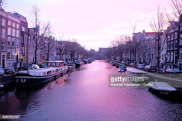 Boats Moored In Canal Amidst Buildings Against Sky During Sunset