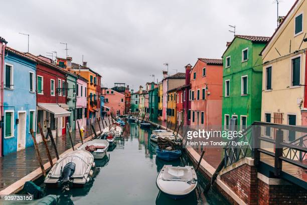 boats moored in canal amidst buildings against sky - burano foto e immagini stock