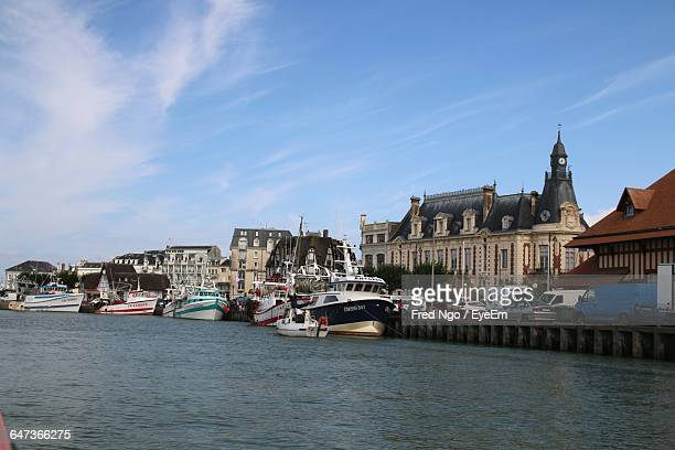 boats moored in canal by buildings against sky on sunny day - trouville sur mer stock pictures, royalty-free photos & images