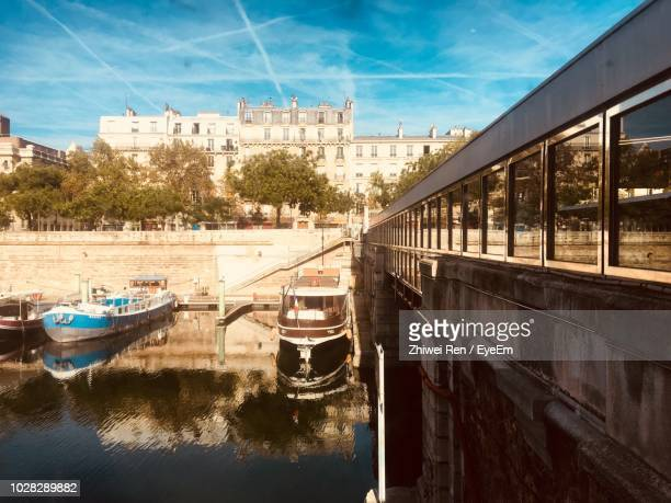 boats moored in canal by buildings against sky - canale foto e immagini stock