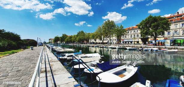 boats moored in canal by buildings against sky - rijeka stock pictures, royalty-free photos & images