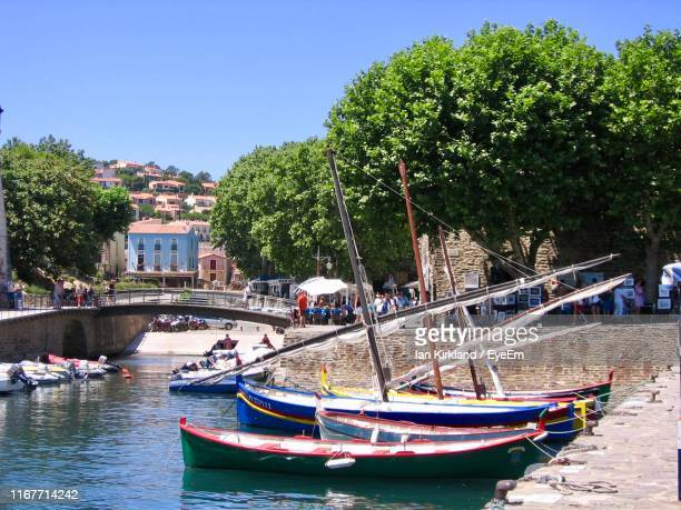 boats moored in canal by city against sky - collioure photos et images de collection